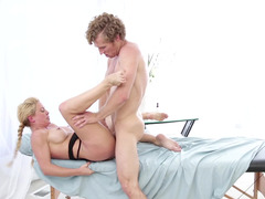 A blonde mature minx is getting touched and fucked on the massage table