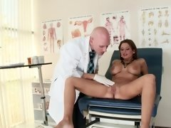 A brunette that has a lovely mouth is sucking on a long pole