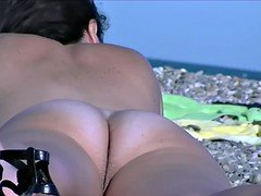 Nudist video at the beach has shy girl playing in the water