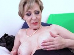 Horny busty granny is teasing in sexy lingerie with a dildo on webcam