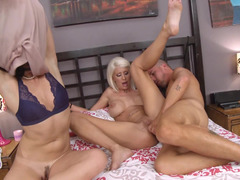 A blonde and brunette are getting humped on the bed by a man