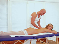 A bitch blonde is on the massage table, getting fucked by the dude