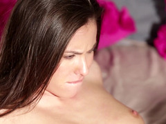 A brunette is getting her body touched while she is on the bed