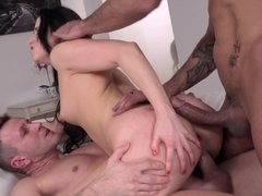 A raven haired girl is receiving two cocks at the same time