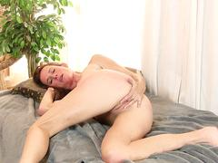 Milf teasing on a bed stripping down and then masturbating on a webcam