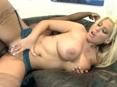 Buxom blonde pornstar relaxes on the leather couch with black man