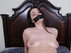 A woman that loves bondage is tied up and fucked on the bed