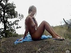 Curly blonde stripping naked outdoors