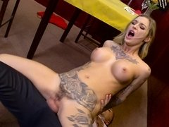 A bimbo blonde with huge fake tits and tattoos is penetrated on the floor