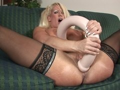A giant toy is getting shoved inside a hot blonde with large tits