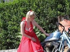 Nice-looking blonde enjoys posing next to a bike
