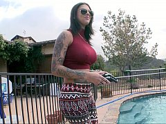 Badass inked model posing by the pool