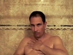 Dark-haired gay daddy plays with his boner in the bathroom