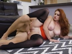 A gorgeous redhead with large tits is fucked on the floor