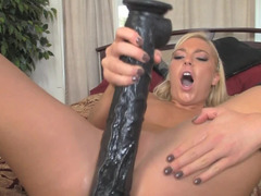 A blonde that is filled with lust is riding a big huge dildo
