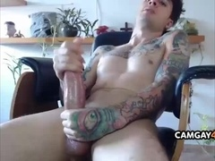 Tattooed Guy Strokes his Huge Cock