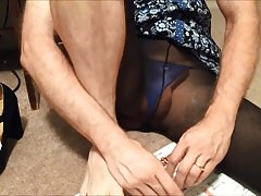 crossdresser putting on nail polish in pantyhose