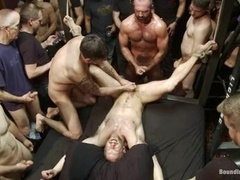 Submissive gay gets suspended and fucked by a few dominators